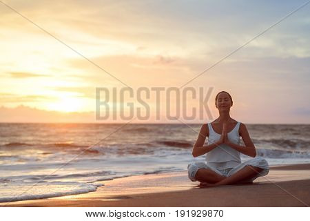 Young girl doing yoga at sunset