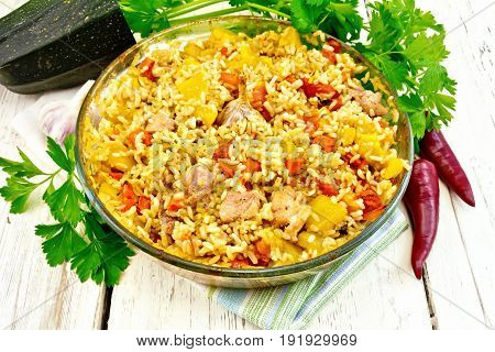 Rice with chicken, tomatoes, carrots, zucchini and garlic in a glass pan on a napkin, parsley and hot pepper on the background light wooden boards