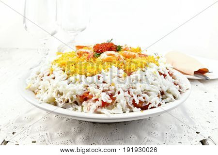 Layered salad of salmon, squid, shrimp, avocado, rice and eggs in a plate, napkin on the background light wooden boards