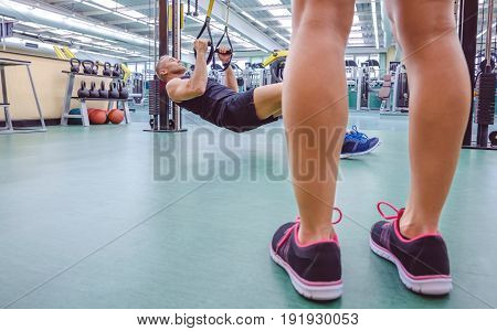 Handsome man doing hard suspension training with fitness straps and female legs in the foreground.