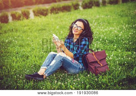 Happy Pretty Girl Using Tablet Pc And Headphones Listening To Music Outdoors.