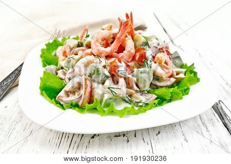 Salad with shrimp, avocado, tomatoes and mayonnaise on the green lettuce in a plate, napkin, fork on the background of the wooden table