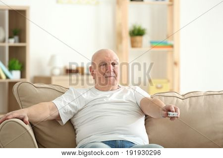 Fat senior man watching TV while sitting on sofa at home. Sedentary lifestyle concept