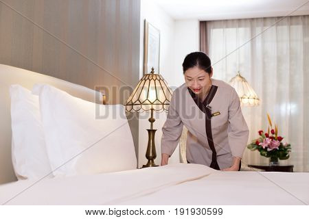 young chinese woman housekeeper makes bed in modern hotel