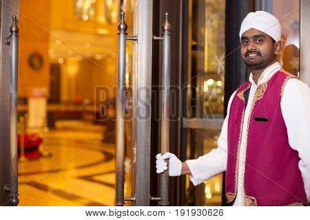 young indian porter service in luxury hotel lobby