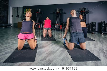 People stretching body in fitness class on sports center