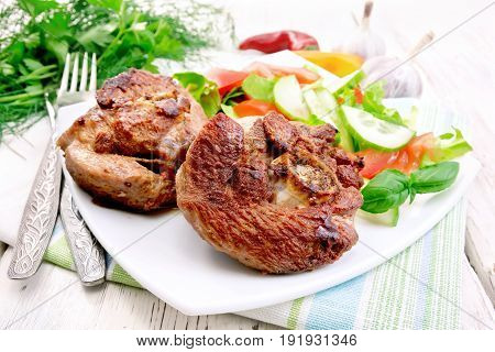 Grilled meat turkey in a white plate with slices of tomato, cucumber, sweet pepper and basil on a wooden boards background