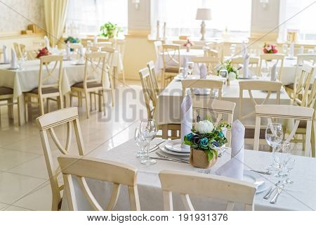 Modern restaurant interior with white wooden chairs and tables