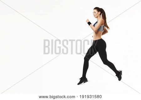 Young beautiful athletic girl in sportswear training running over white background. Copy space.