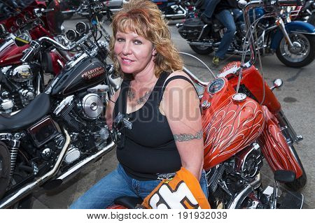 Sturgis South Dakota - August 8 2014: Woman Rider sitting on her bike in the city of Sturgis in South Dakota USA during the annual Sturgis Motorcycle Rally