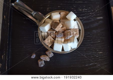 Top view sugar bowl with lumps of white and brown sugar in restaurant