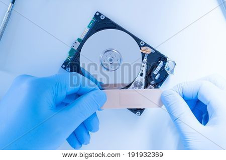 Lab engineer repairing and fixing broken hard disk for data recovery