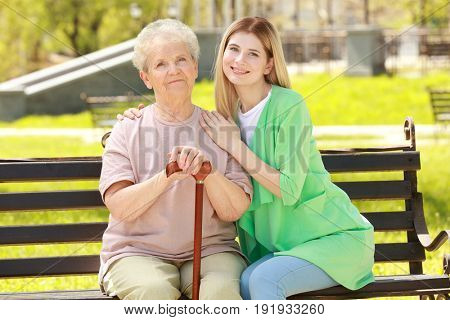 Elderly woman and young caregiver in park on sunny day