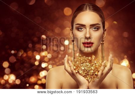 Woman Gold Beauty Fashion Model Holding Golden Jewelry in Hands
