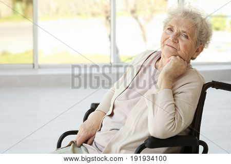 Disabled elderly woman in wheelchair at home