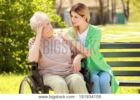 Disabled elderly woman and young caregiver in park on sunny day