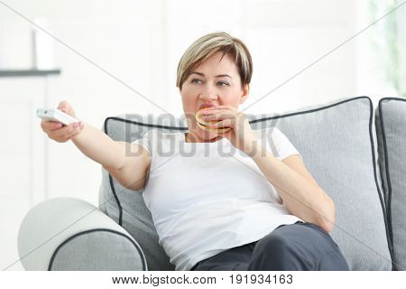Mature woman watching TV and eating hamburger while sitting on sofa at home. Sedentary lifestyle concept