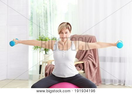 Mature woman training with dumbbells at home. Weight loss concept