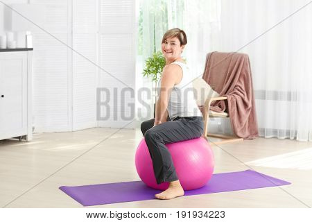 Mature woman training with fitball at home. Weight loss concept