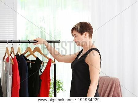 Mature woman near rack with small-sized clothes at home. Weight loss concept