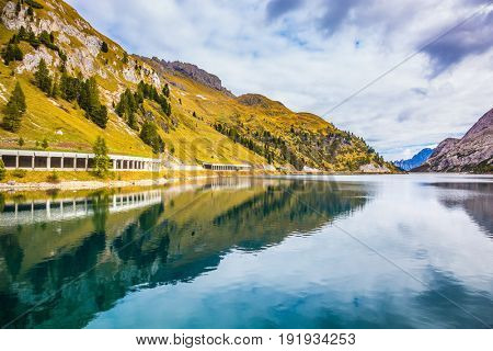 Mountain Lake Lago di Fedaia, Dolomites. Glacial lake with clear cold water. Cool autumn day. The concept of ecological and extreme tourism