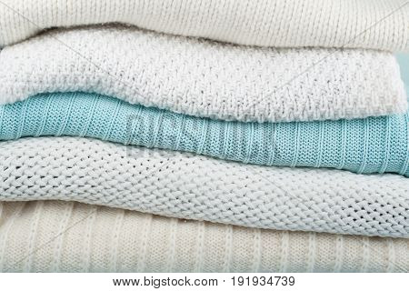 Knitted wool sweaters. Pile of knitted winter clothes on wooden background, sweaters, knitwear, space for text poster