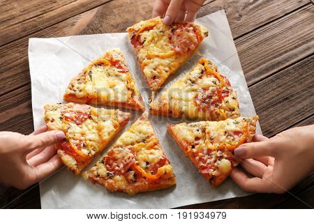 Hands taking pizza slices from napkin, close up view