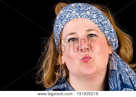Portrait of a attractive european light overweighted red haired female sending kisses, wearing blue lumberjack shirt and blue scarf as headwear, headshot, studio in front of dark background