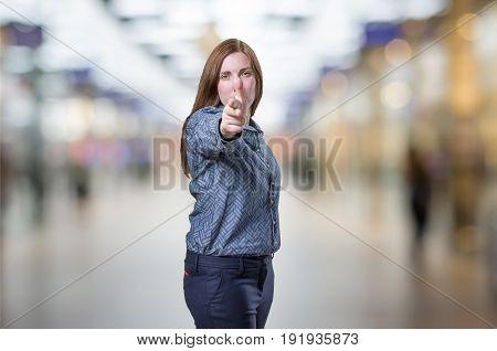 Pretty Business Woman Making Gun Gesture Over Blur Background