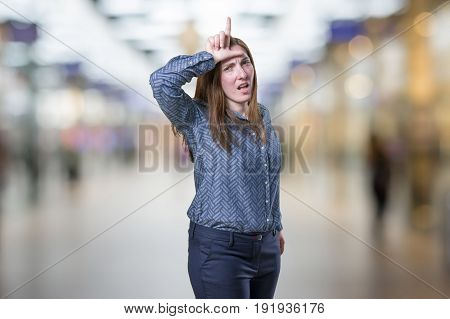 Pretty young businesswoman making loser sign over blur background.