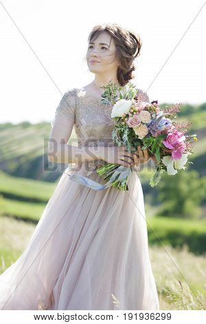 Portrait of a beautiful bride with a bouquet in the nature. fine art photography.
