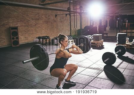 Young woman squatting while holding heavy barbell on shoulders in light gym.