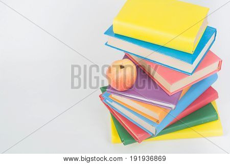 Stack of colorful real books, apple on white background, partial view. Back to school, Copy Space. Education