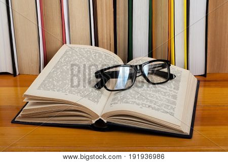 Open book, glasses hardback colorful books on wooden table. Back to school. Copy space for text. Education business concept