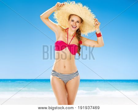 Portrait Of Happy Young Woman In Straw Hat On Beach
