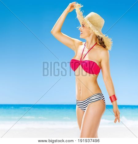 Perfect summer. Portrait of smiling active woman in straw hat on the seacoast