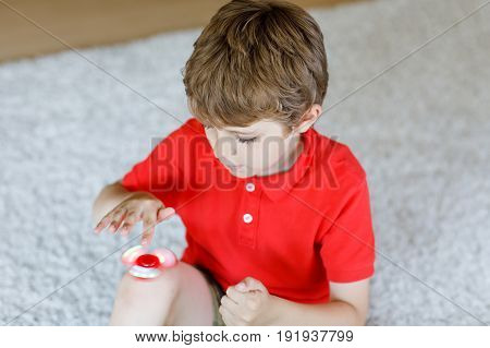 School kid playing with Tri Fidget Hand Spinner indoors. Popular and trendy toy for hands for children and adults. summer trend of 2017. red hand spinner, fidgeting toy rotating on child's hand