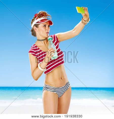 Woman On Seacoast With Smoothie Taking Selfie With Cellphone