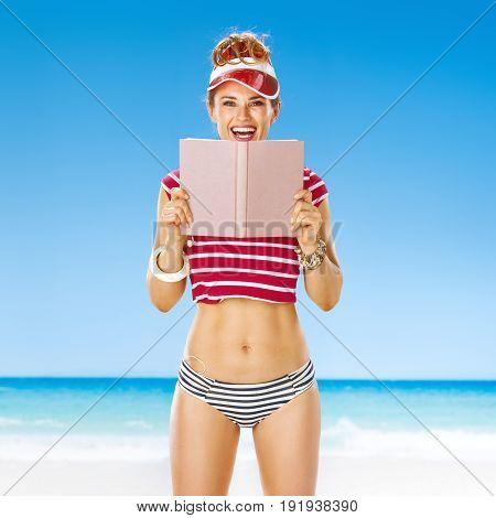 Perfect summer. smiling healthy woman in red sun visor on the beach with book