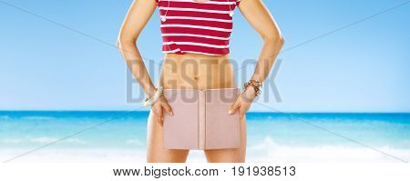 Perfect summer. smiling active woman in red shirt on the seacoast hiding behind book