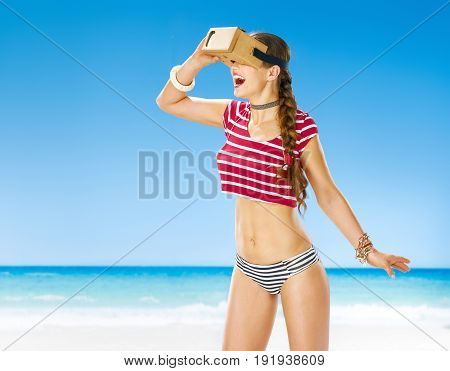 Perfect summer. happy active woman on the seacoast in cardboard virtual reality gear