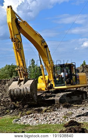 Unidentified excavating operator moves earth in a summer construction project