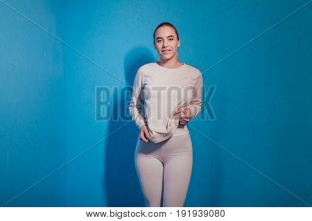 Sexy blonde woman in a grey sweatshirt on blue background. Mock up.