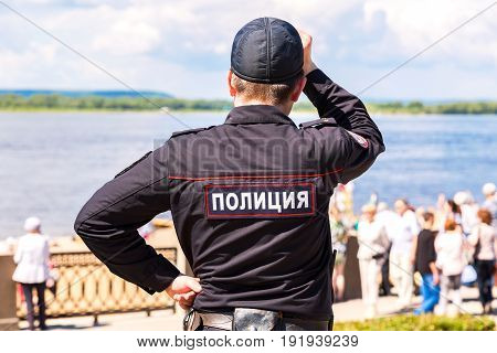 Samara Russia - May 12 2017: Unidentified Russian police officer in uniform at the embankment of Volga river. Text in russian: