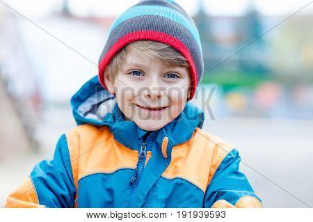 Outdoor fashion portrait of adorable little kid boy wearing colorful clothes. Spring, summer or autumn fashion for boys and children. Schoolkid
