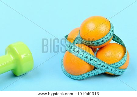 Dumbbell In Light Green Color Near Oranges With Measuring Tape