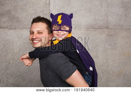 Side view of happy man holding kid in superhero costume on back and smiling at camera.