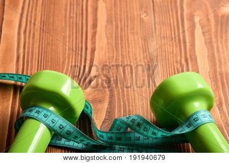 Tape For Measuring In Yellow Color Wrapped Around Green Dumbbells