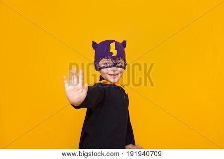 Smiling kid in knitter hero hat holding hand forward showing stop gesture on orange background.