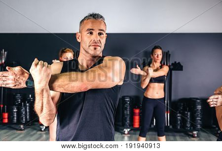 Portrait of man stretching arms in fitness class on sports center